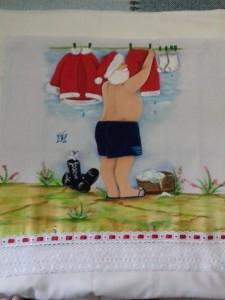 Pano de Prato com pintura do Papai Noel lavando roupa e bico com renda.